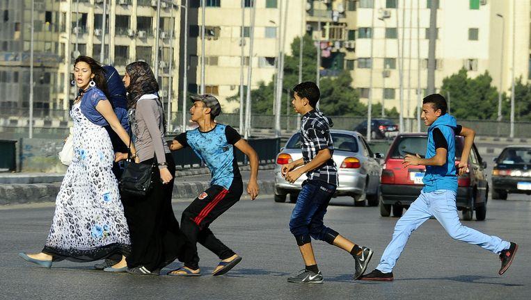 Jongeren vallen een ongesluierde vrouw lastig in Caïro in Egypte. De man-vrouwverhouding blijft problematisch in de islamitische cultuur. Beeld © Ahmed Abd El Latif/AP