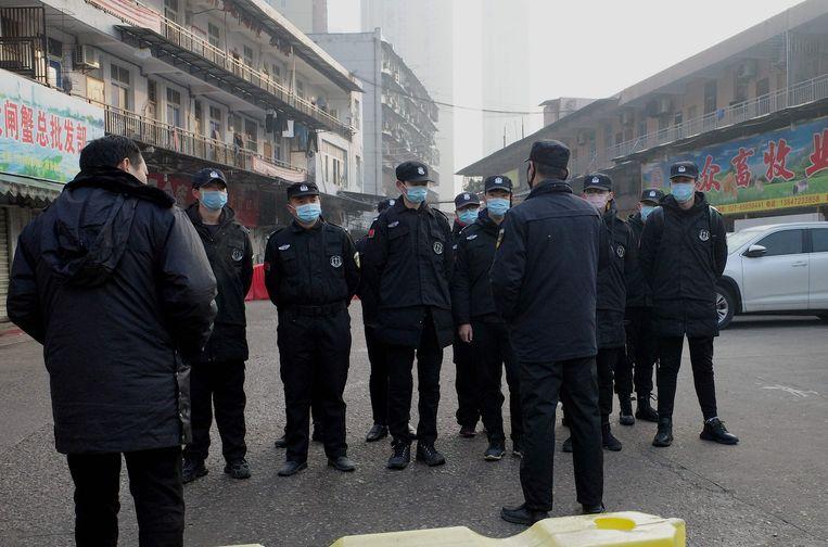 Beveiligers staan voor een gesloten dierenmarkt in Wuhan, waar een slachtoffer van het nieuwe virus inkopen had gedaan.  Beeld AFP