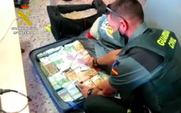 Een politieman toont de valiezen van de Belgische bestuurder, bomvol met bankbiljetten.