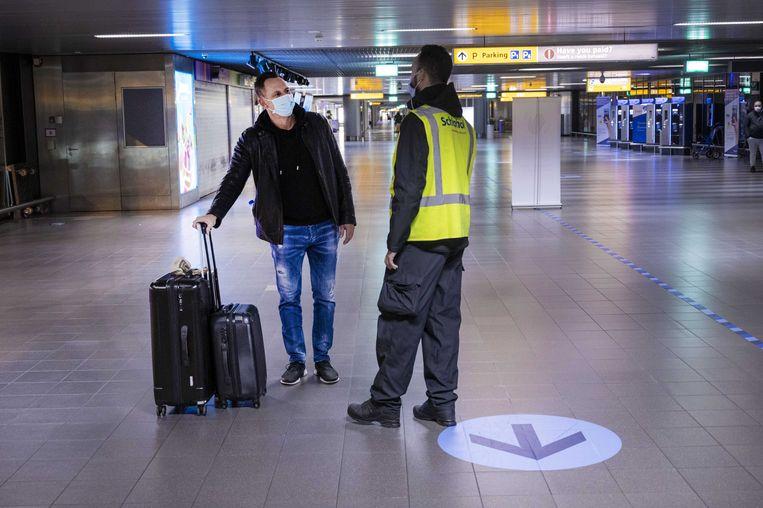 Medewerkers controleren bezoekers op Schiphol. Beeld ANP