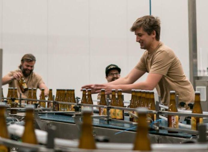 De flesjes worden handmatig in de gerecycleerde bakken gestopt.