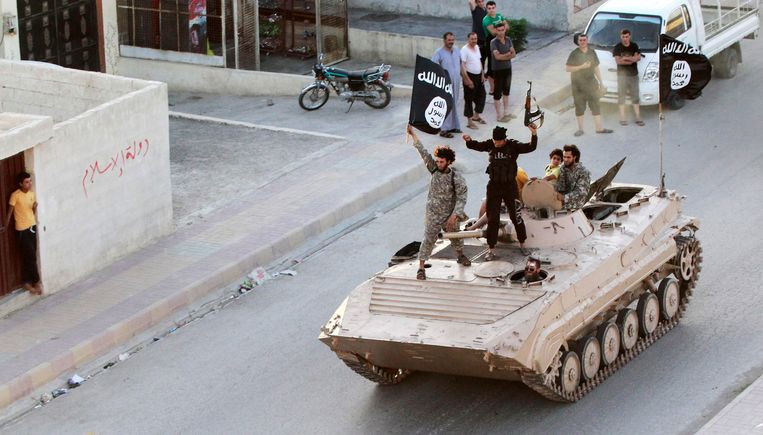 Militant Islamist fighters hold the flag of Islamic State (IS) while taking part in a military parade along the streets of northern Raqqa province in this June 30, 2014. Beeld REUTERS