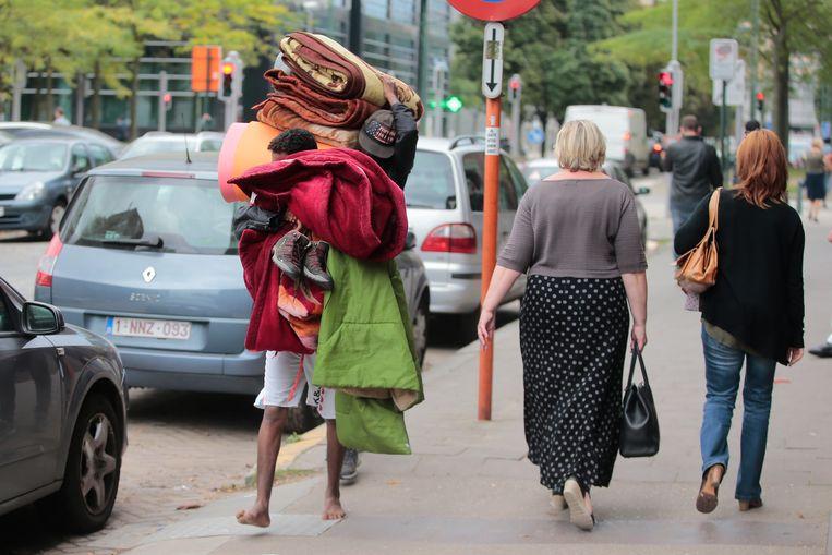Archiefbeeld: een vluchteling loopt met heel zijn hebben en houden door Brussel.  Beeld Photo News