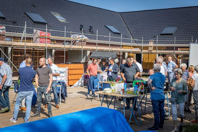 De bouwvakkers, de bewoners en andere genodigden vieren dat de bouw van wooncomplex Noabershof op 'n Esch al vergevorderd is.