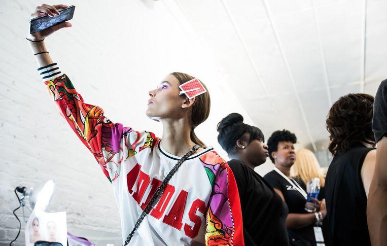 Een model neemt backstage een selfie van haar look. Beeld kos