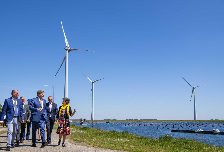 Koning Willem-Alexander wandelt met Teus Baars van Zeeuwind en Monique Sweep van Deltawind door Windpark Krammer, het grootste turbinepark dat in Nederland in handen van burgers is.