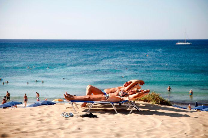 Toeristen zonnebaden op het strand van de badplaats Ayia Napa in Cyprus.