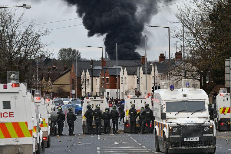 Politie raakt slaags met demonstranten in West-Belfast, met op de achtergrond de rook van een uitbrandende bus. Beeld Reporters / Splash