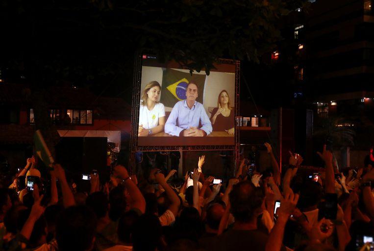 Aanhangers van Jair Bolsonaro kijken naar een videospeech na zijn overwinning in de Braziliaanse presidentsverkiezingen. Beeld REUTERS