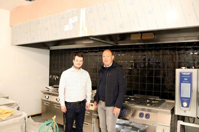 Rogier en Koenraad in hun vernieuwde keuken, waar de brand acht maanden geleden was ontstaan.