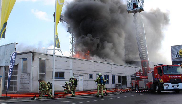 Een grote rookwolk stijgt op uit het dak.
