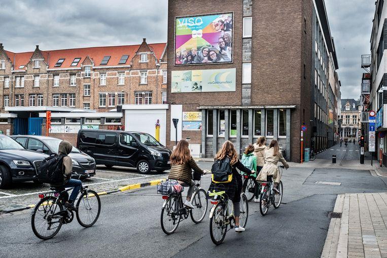 Leerlingen komen na schooltijd uit de schoolpoort gereden in Roeselare. Beeld Tim Dirven