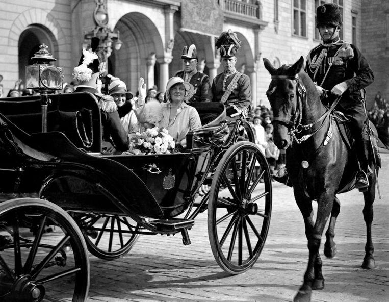 Koningin Wilhelmina zwaait naar het volk bij het vertrek vanaf het stadhuis voor een rijtoer door Rotterdam, 1930. Beeld anp