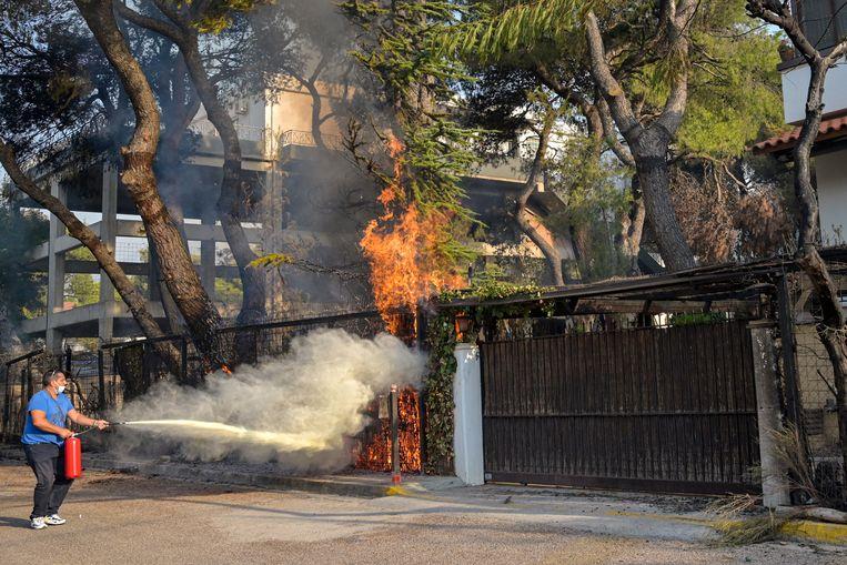Een inwoner van Athene probeert een brand te blussen. Beeld Getty Images