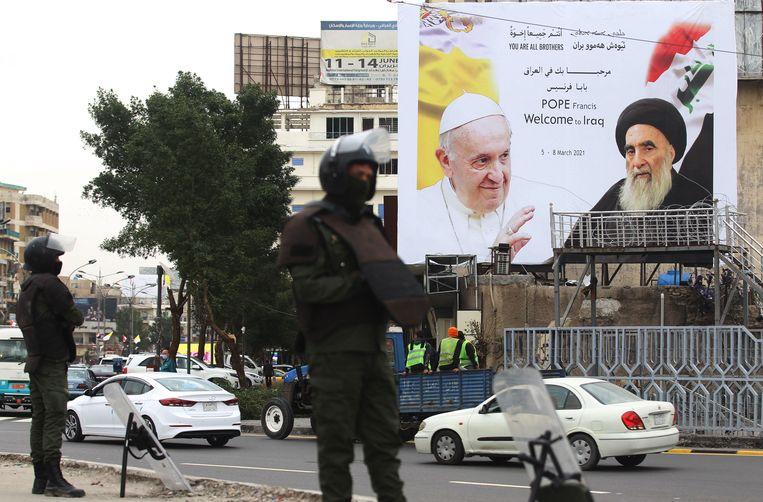 Een billboard toont paus Franciscus en grootayatollah Ali al-Sistani, de belangrijkste sjiitische geestelijke leider van Irak.  Beeld AFP