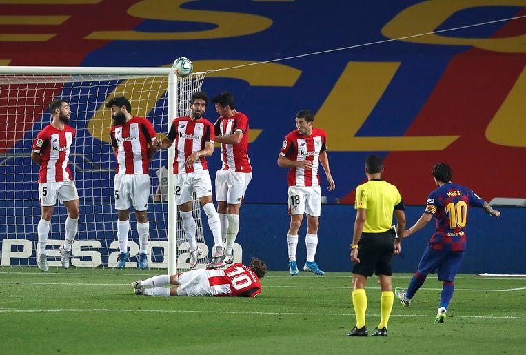 Messi (Barcelona) schiet de vrije trap hoog, want het gat onder de muur is afgedekt. Beeld Getty Images