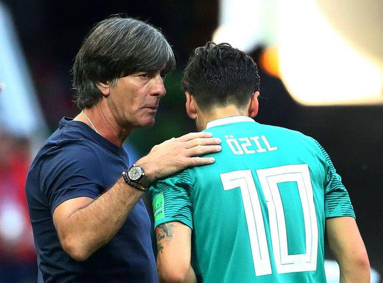 Joachim Löw geeft zijn middenvelder Mesut Özil raad in de fatale match tegen Zuid-Korea. Beeld Photo News