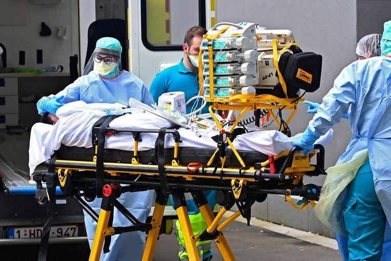 Patiënten worden overgebracht naar de MountLegia-kliniek in Luik. De opening van het nieuwe ziekenhuis is versnel door de corona-epidemie. Beeld Photo News