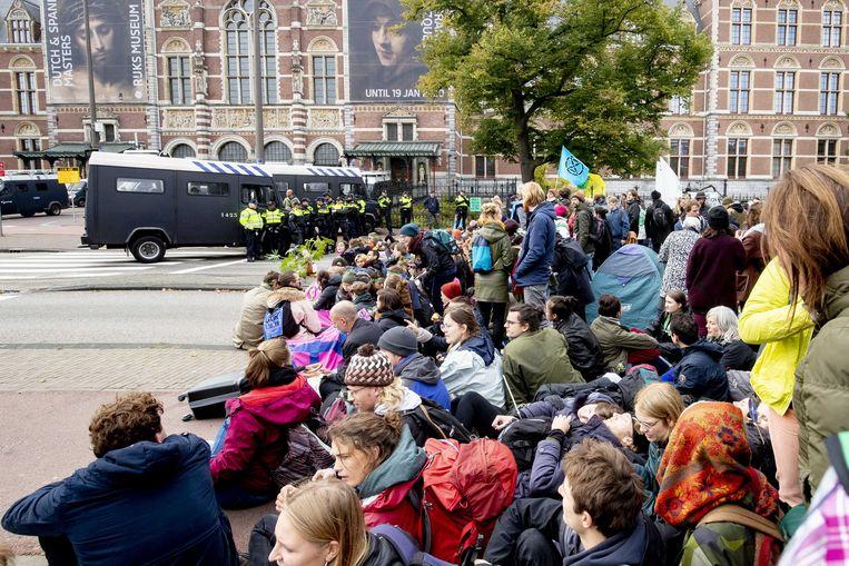 Activisten van Extinction Rebellion blokkeren de Stadhouderskade in Amsterdam. De actievoerders negeren daarmee het verbod van de gemeente voor de actie. Op de achtergrond het Rijksmuseum. Beeld ANP