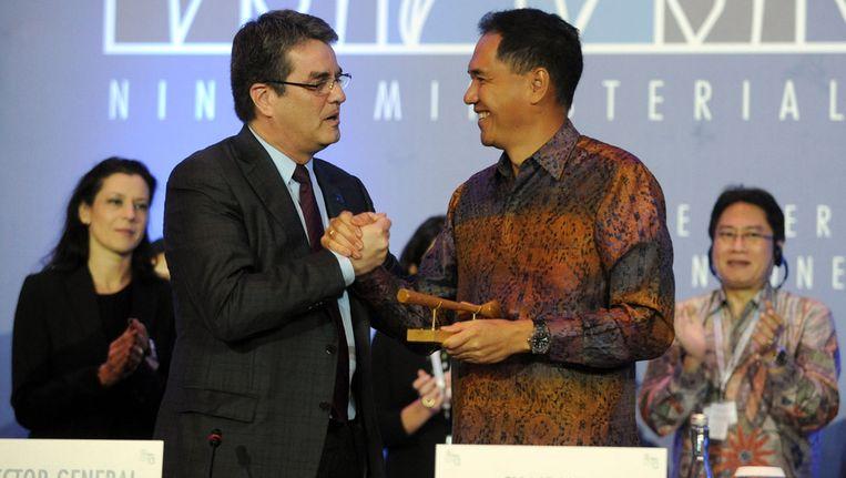 Directeur-genraal van de WTO, Roberto Azevedo, schudt voorzitter van de conferentie, Gita Wirjawan (R) de hand na het bereiken van een akkoord Beeld afp