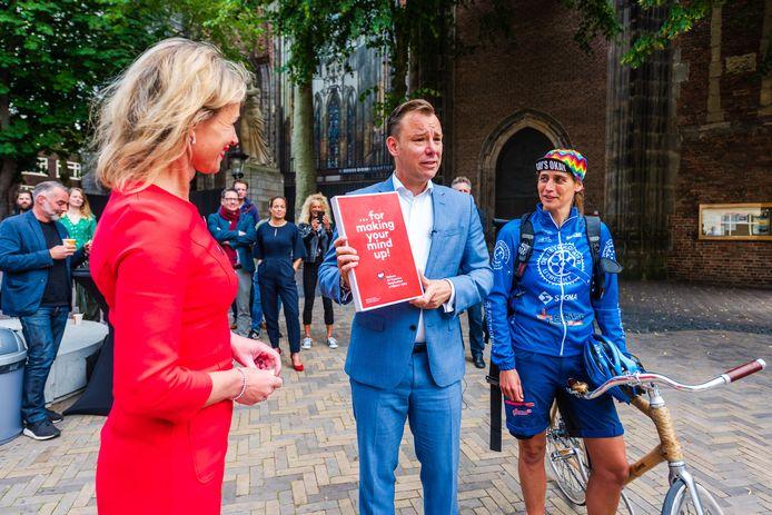 De Utrechtse D66-wethouder Klaas Verschuure met het bidbook even voordat hij het stuk, namens de gemeente Utrecht, aan een fietskoerier meegeeft.