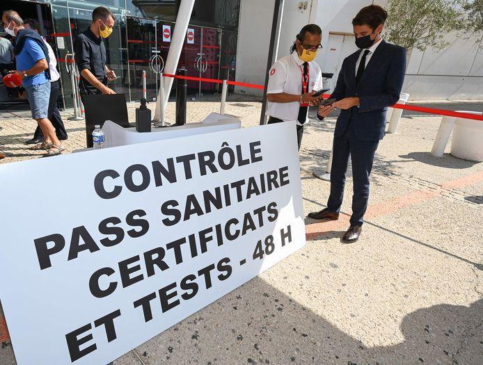 """Le secrétaire d'État français et porte-parole du gouvernement, Gabriel Attal (R), montre son """"pass sanitaire"""" à un fonctionnaire lors de sa visite au cinéma Gaumont Multiplex Odyséum à Montpellier, dans le sud de la France, le 29 juillet 2021."""