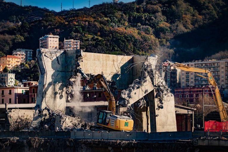 Bulldozers zijn bezig aan de afbraak van de brug. Binnen een jaar zou er een nieuwe moeten zijn, maar niemand die dat gelooft.  Beeld JONAS LAMPENS
