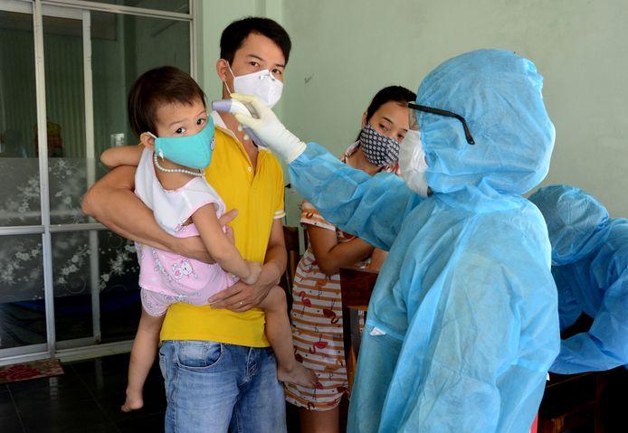 Een zorgverlener test inwoners van Da Nang nadat drie nieuwe coronabesmettingen werden vastgesteld.
