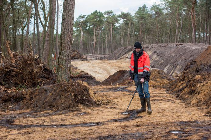 Archeoloog Lucas Meurkens bij de donkere contouren van grafheuvels in de bodem, daar waar straks een nieuwe weg wordt aangelegd.
