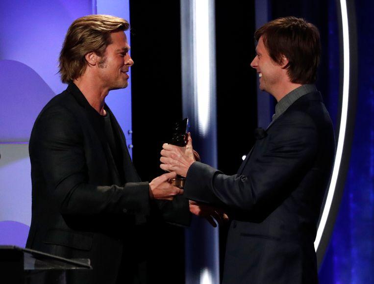 Felix Van Groeningen krijgt zijn award van Brad Pitt tijdens de Hollywood Film Awards.