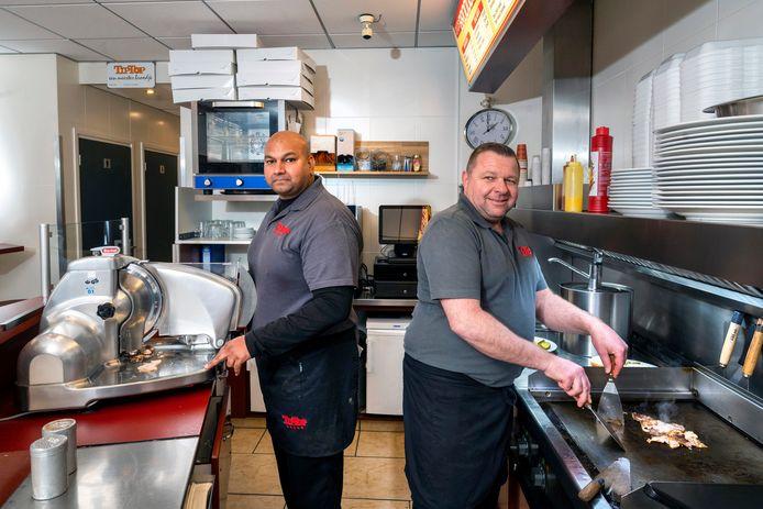Wirdjanand Bhola (links) en Danny Massop maken een broodje warm vlees.