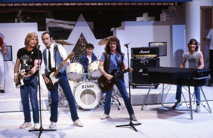 Status Quo tijdens een optreden, met Lancaster in het midden op bas.