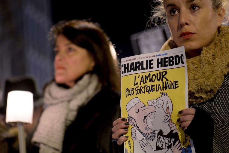 Een vrouw houdt een editie van het tijdschrift Charlie Hebdo omhoog bij een herdenking bij het Franse consulaat in Barcelona. Beeld afp
