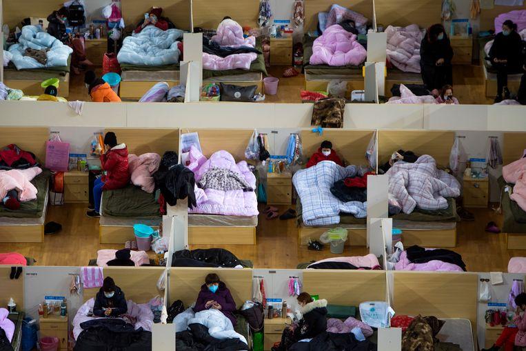 Patiënten besmet met het Covid-19-virus worden opgevangen in een omgebouwd sportcomplex in Wuhan. 'In de provincie Hubei kunnen ziekenhuizen de toevloed niet aan en sterven mensen die in normale omstandigheden gered kunnen worden.' Beeld AP