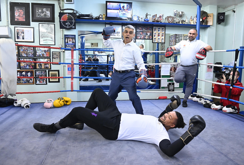Khan voert campagne in een boksschool in Zuid-Londen. Liggend op de grond wereldkampioen bij de zwaargewichten Joe Joyce. Beeld EPA