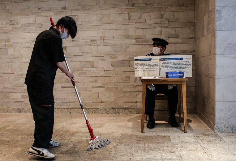 Een veiligheidsofficier kijkt toe hoe een schoonmaker de vloer boent. Veiligheid en gezondheid spelen een hoofdrol tijdens de Olympische Spelen.  Beeld Anadolu Agency via Getty Images