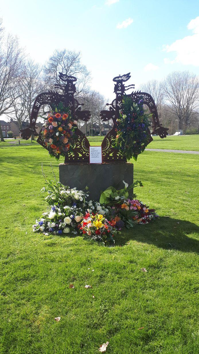 Bloemen bij het beeld van De Ontmoeting in Beek en Donk voor alle corona-slachtoffers.