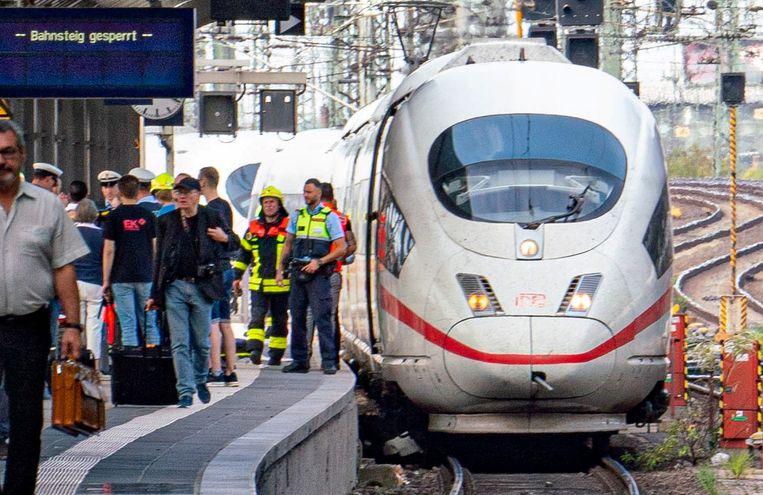 Politie en hulpverleners staan naast de trein waaronder de 8-jarige jongen samen met zijn moeder geduwd werd. Beeld AFP