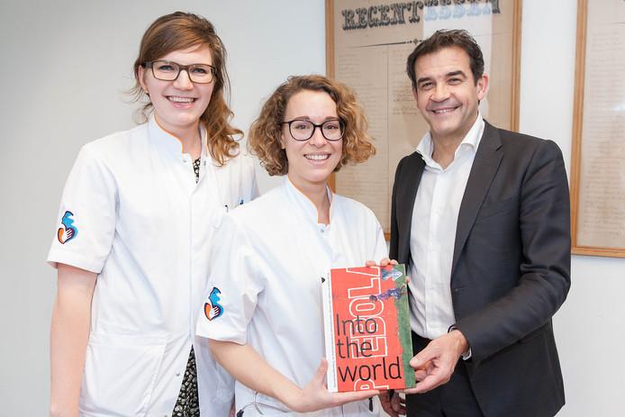 AIGT's in opleiding Heleen Koudijs (links) en Anne van der Breggen schenken een exemplaar van het boek 'Into the World' aan Peter van der Meer.
