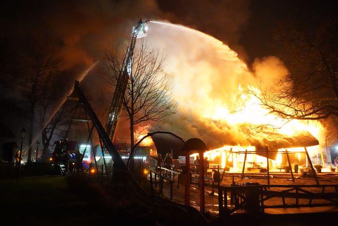 De vlammen slaan uit het rieten dak van het theatergebouw op het terrein aan de Ringdijk.