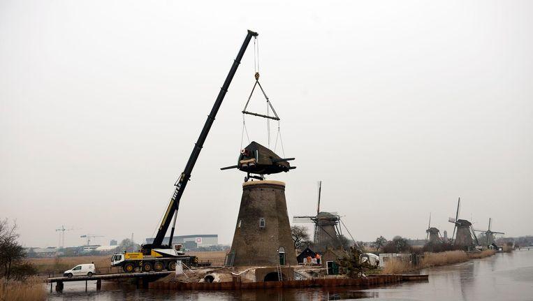 Bij de restauratie van een molen aan de Kinderdijk wordt het dak gelicht. Beeld null