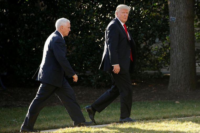 Donald Trump en Mike Pence lopen terug naar het Witte Huis. Beeld reuters