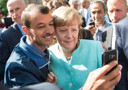 Een vluchteling neemt een selfie met Angela Merkel