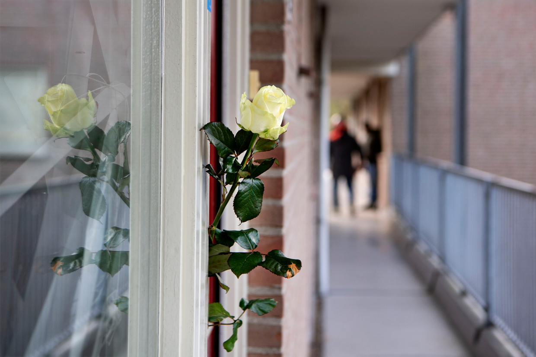 Buren hebben rozen neergelegd bij de woning van de vrouw die is overleden aan haar verwondingen nadat zijn gisteren in verwarde toestand door de politie was neergeschoten.