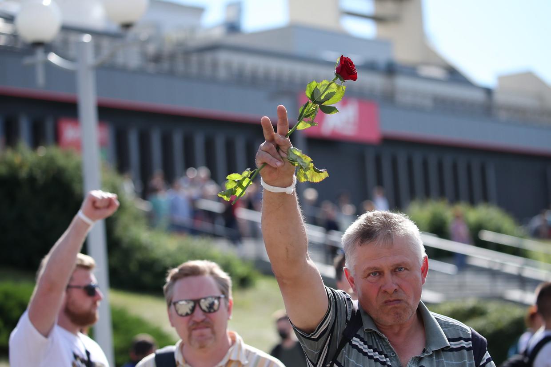 Betogers in Minsk brengen hulde op de plek waar iemand overleed na confrontaties met de ordetroepen van Loekasjenko.  Beeld EPA