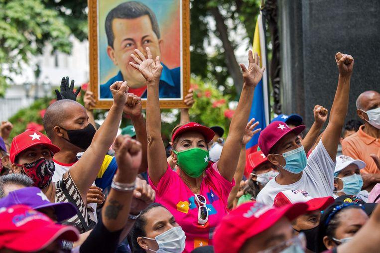 Aanhangers van Nicolás Maduro met een portret van zijn voorganger, Hugo Chávez.    Beeld AFP