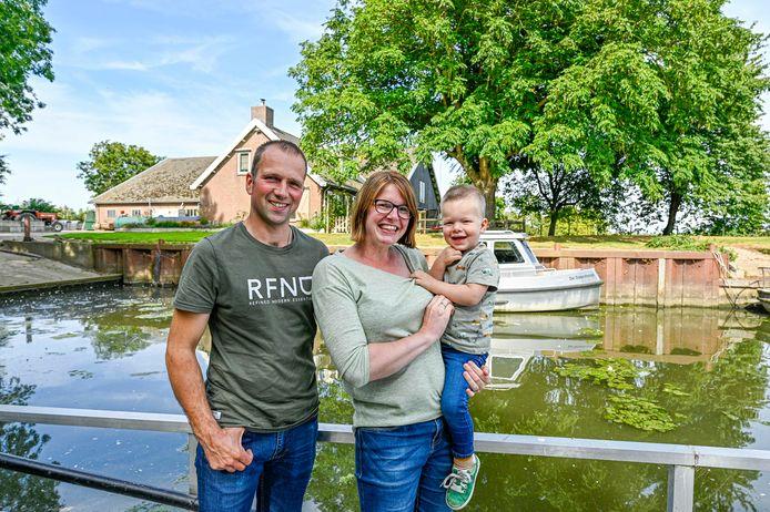 Jan en Nancy Saarloos met hun zoontje Naud bij hun eigen haventje bij de Vischplaat. Achter hen staat hun boerderij.