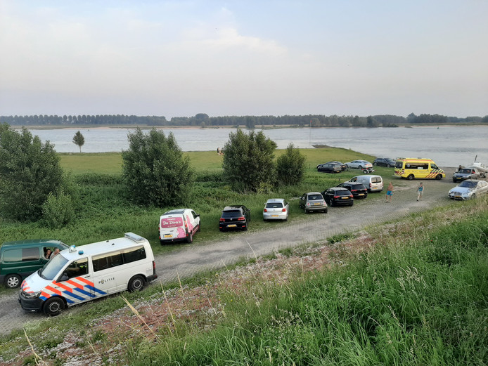 Hulpdiensten langs de Waal bij Hellouw nadat een persoon te water is geraakt.