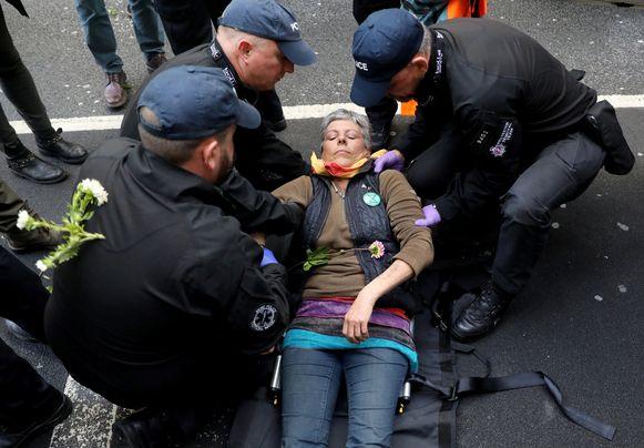 Een manifestante laat zich oppakken in Londen.