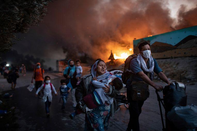 Migranten vluchten weg uit het vluchtelingenkamp Moria op Lesbos, nadat daar voor de tweede keer in twee dagen brand is uitgebroken. Archiefbeeld van september vorig jaar. Beeld AP